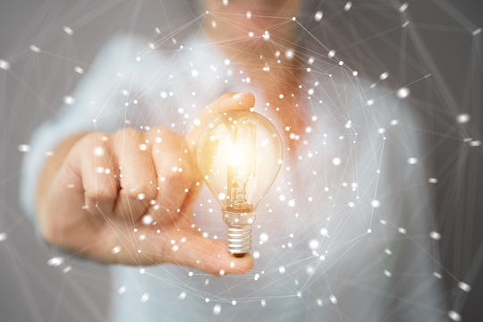 Businesswoman holding a lighbulb with connections in her hand