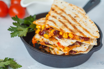 Vegetarian quesadilla with vegetables and cheese in cast iron frying pan