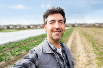 Attractive middle aged farmer taking selfie in the midle of a field