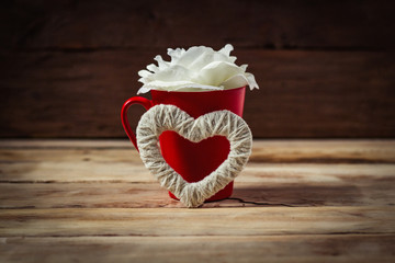 White rose flower in a red cup and the heart of a handmade. Valentine's day concept