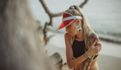 Portrait of a beautiful girl in a red visor closeup. Wearing Large turquoise earrings. Holiday in Thailand On the background of evening beach