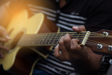 Close-up of men playing acoustic guitar. warm tone. American Artist playing to music.