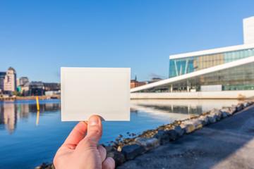 Tourist hält Sofortbild vor Skyline von Oslo, Norwegen