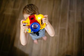 Cute boy becoming photographer