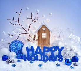 "Greeting ""Happy Holidays"", decorative balls and toy house on a background of christmas lights."