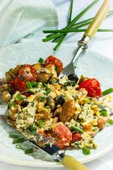 Rührei mit Pilzen, Tomaten, Schnittlauch auf einem Teller mit Messer und Gabel