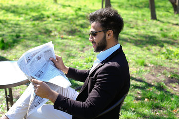 Embarrassed young man reading newspaper.