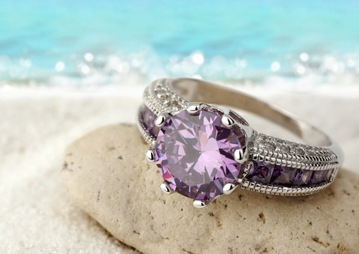 Jewelery ring with violet gemstone on sand beach with copy space