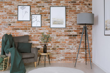 Grey armchair against brick wall