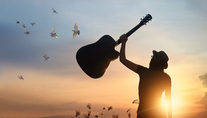 Musician raising guitar over head with free bird of silhouette on sunset nature background