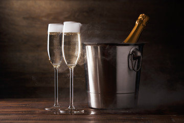 Picture of two wine glasses with sparkling wine, iron bucket