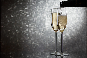Photo of bottle with pouring champagne in wine glasses on gray background