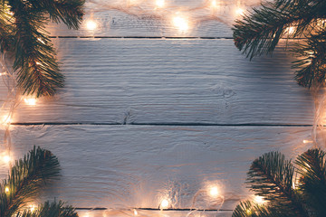 Photo of Christmas wooden gray surface with burning garland, branches of spruce.