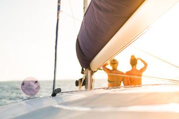 Women in bikini on the sailing boat watching the sea and horizon, sunset mood