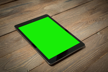 Tablet su tavole di legno con green screen