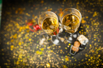 Two champagne glasses in golden glitter