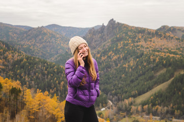 A girl in a lilac jacket talking on the phone in the mountains, an autumn forest with a cloudy day, free space for text
