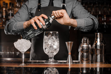 Barman in the apron making a cocktail with help of bar equipment
