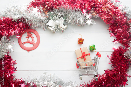 Creative flat lay of Christmas ornaments and gift boxes in shopping cart, Christmas online shopping