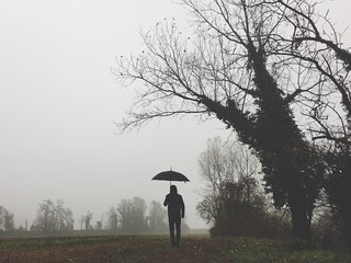 ragazzo vestito di nero con ombrello nella nebbia