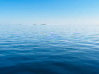 Smooth Blue Water Of The Sea With Island In The Distance