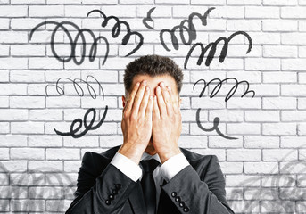 Stressed man covering face