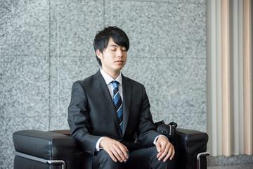 会社のロビーで座って待つ男性(目をつぶる)