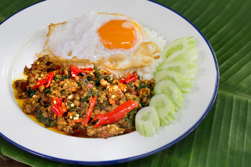 Spicy Stir fried chicken chopping with basil leaves and fried egg Thai food in white dish on green banana leaf