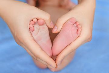 heels of newborn in mother hands forming a heart