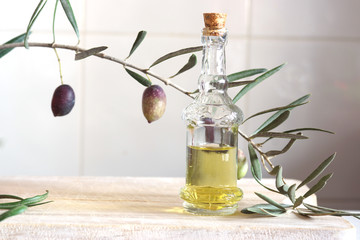 Still life with olive branch and olive oil in a bottle on a wooden cutting board.