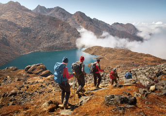 Group tourists with Backpacks descends down on Mountain Trail during Hike.
