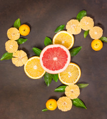 Fresh citrus fruit assortment. Different citrus fruit on black slate table. Fruit food background. Healthy eating and diet.