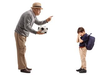 Mature man with a deflated football scolding a little boy