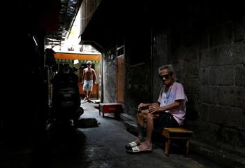An old man sits in an alley entrance where Rolando Arellano Campo, Sherwin Bitas and Ronnie Cerbito were killed in Tondo, Manila