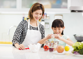 Happy mother and child in kitchen preparing cookies.