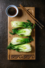 Stir fried bok choy or chinese cabbage with soy sauce served on decorative wooden cutting board with chopsticks over dark texture background. Top view with space. Asian style dinner