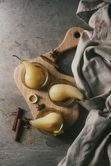 Traditional dessert poached pears in white wine served in glass bowls with syrup and lemon zest on wooden serving board over gray texture table. Top view with space