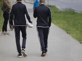 two of the same guy walking on the sidewalk