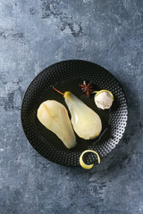 Traditional dessert sliced poached pears in white wine served in black plate with syrup, ice cream and lemon zest over blue texture background. Top view with space