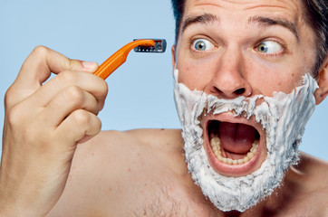 Man with a beard on a light background holds a razor in a shaving foam, emotions, portrait