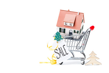 Image of cart with house, Christmas tree, greeting card, ribbon on empty white background.