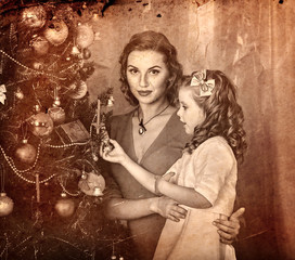 Christmas photo with mother and daughter put up decorations. Family with child wait father. Black and white Xmas vintage image with child by home interior.