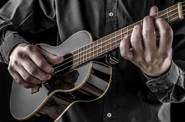 musician playing black tenor ukulele