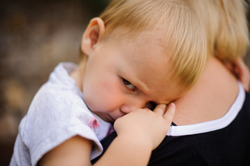 Cute blonde child lying on mom's shoulder