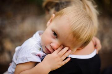 Little blonde child lying on mom's shoulder