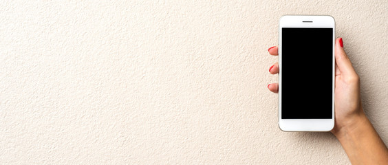 Female hand holding white mobile phone. Close up
