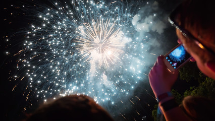 Woman photographing fireworks celebration