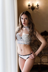 Attractive young woman dressed in a  white lace underwear standing near a window in a hotel room.
