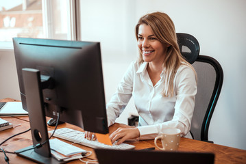 Image of cheerful blonde woman working on computer.