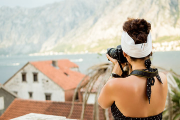 Woman photographer takes pictures of mountains in the summer
